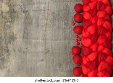red wool for felting and place for text on wooden background