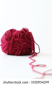 red wool yarn ball on white background