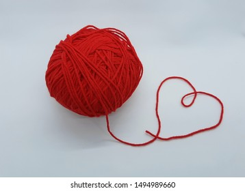 red woolen crochet yarn ball with heart tangled tip isolated on white background