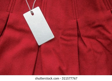 Red woolen pleated skirt with blank tag on white background.