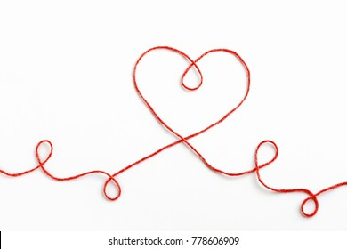 Red woolen thread in the shape of heart on white background. Valentine's Day