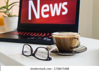 Red word news on the laptop screen. Glasses and a Cup of coffee are on the white table.