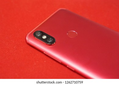 Red Xiaomi Mi A2 phone on red background