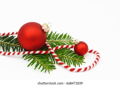 red xmas bauble with fir branch and  ribbon on white