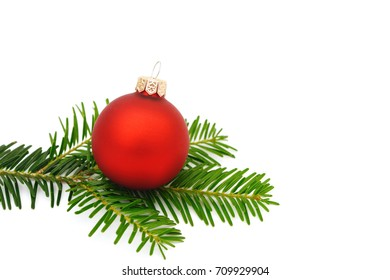 red xmas bauble with fir branch on white