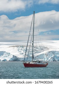 red yacht and glacier around harbour in Antarctica