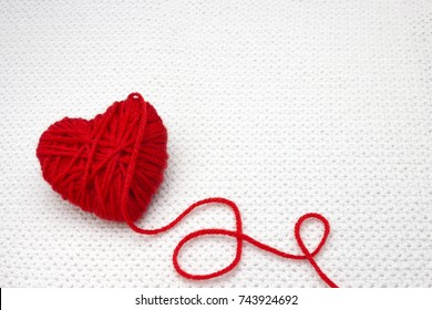 Red yarn ball like a heart on the white crochet background. Romantic Valentines Day or Christmas concept. Red heart made of wool yarn. Festive photo with place for text, copyspace. Knitting with love