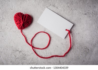 Red yarn heart shaped with white note card on the wall background