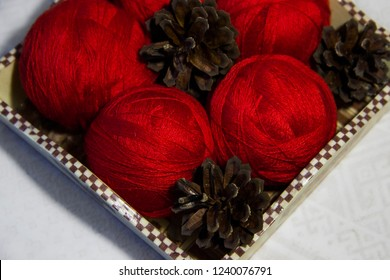 Red yarn for knitting in a basket and pine cones on a white background. Basket with balls of wool. Red knitting wool.