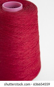 Red yarn on cone, white background, red thread