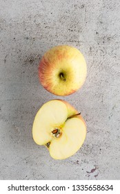 Red and yellow apples fruit on table concrete modern background. Whole and cut.