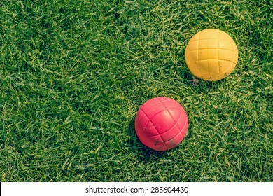 Red and yellow ball of a boccia garden game on the lawn
