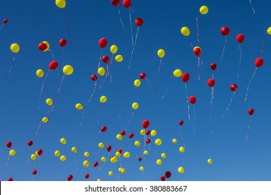 Red and yellow balloons filling a clear blue sky