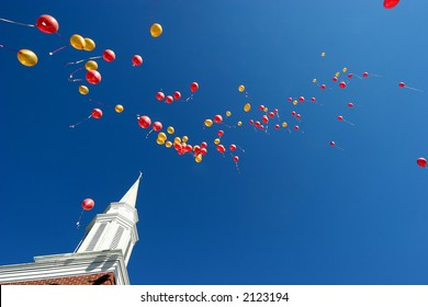 red and yellow balloons floating skyward after a wedding