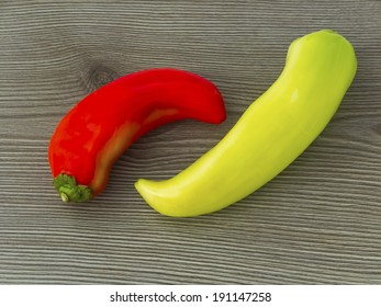 Red and yellow banana peppers on wooden background