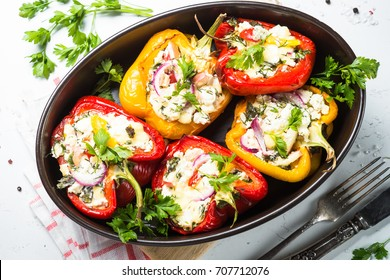 Red and yellow bell stuffed paprika peppers with cheese and herbs. Top view on white background.