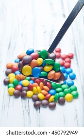 Red, yellow, blue, orange candy or vitamins. Many multicolored bubbles in the background.