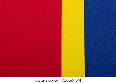 Red, yellow and blue sheets of colored velvet paper. Bright color background. Horizontal orientation. Square and vertical strip. Top view flat lay with copy space.