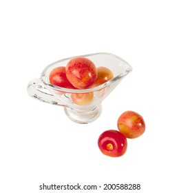 Red and yellow cherries in glass vase isolated on white background