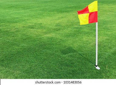 Red and yellow color flag pole on green grass football field corner on bright sunny day,outdoor activity