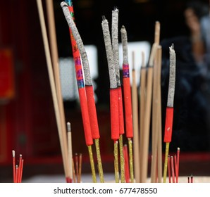 Red and yellow color incense stick burning in the incense burner, burn three sticks for worship.