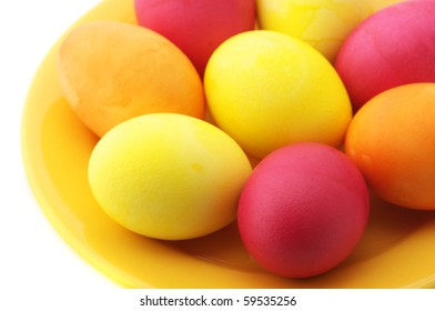 Red and yellow Easter eggs in yellow plate on white background.