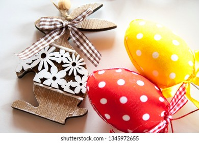 Red and yellow easter eggs with polka dots and wooden bunny