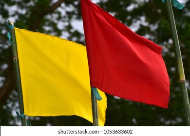 Red & yellow flying textile made flags with natural background unique stock photo