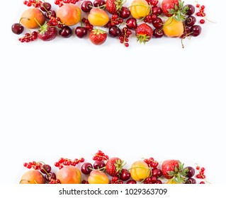 Red and yellow fruits on white background. Ripe apricots, red currants, cherries and strawberries. Sweet and juicy fruits  at border of image with copy space for text. Various fresh summer. Top view