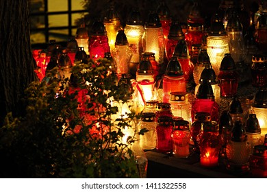 Red and yellow grave candles burning bright in a cemetery at night. Memory of the deceased concept.