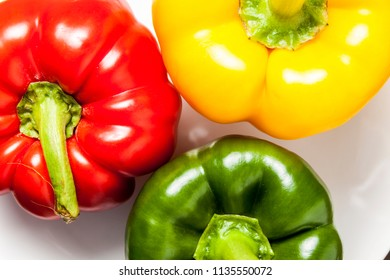 Red, yellow and green bell peppers isolated on white background