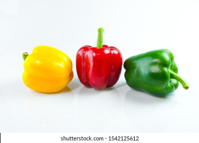 Red, yellow, green bell peppers on a white background