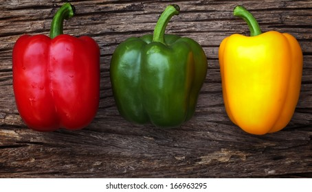 Red, yellow and green bell peppers isolated on the wood background