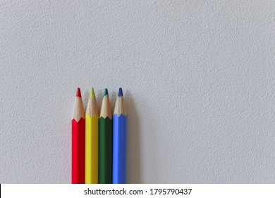 Red, yellow, green and blue pencils are standing in front of a white wall