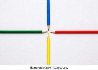 Red, yellow, green and blue pencils on a white sheet of paper