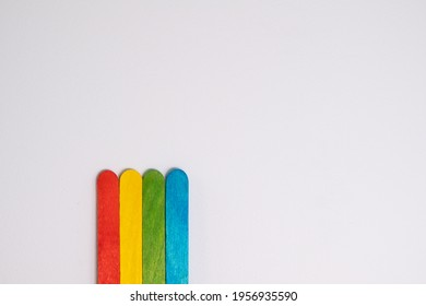 Red, yellow, green and blue wooden sticks standing in front of a white wall