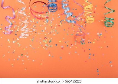 Red, yellow and green heart and circle confetti on a ORANGE background.