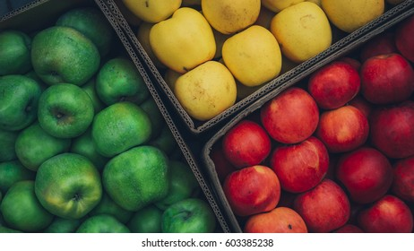 Red and yellow and green juicy apples in a box. apple background.