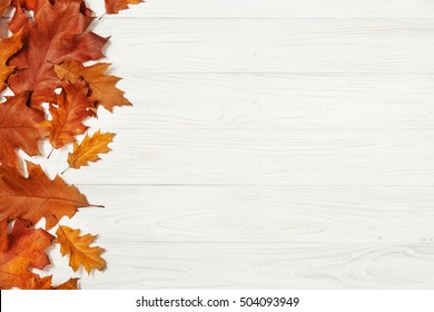 Red and yellow oak leaves on white wooden table
