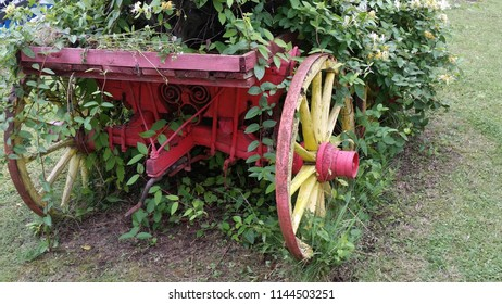 Red And Yellow Old Wagon Wheel With Flowers.Two Old Wooden Wagon Wheels In A