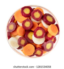 Red, yellow, and orange carrot slices in bowl and isolated on a white background