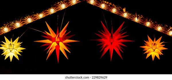 Red, yellow and orange Morovian stars hang from an illuminated gable at a Christmas market