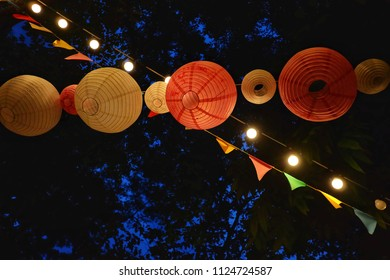 Red yellow paper lamps hanging on the trees with a line of light bulb glowing in outdoor fair area
