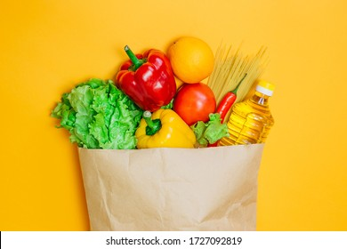 Red, yellow pepper, chili, sunflower oil, tomato, orange, pasta, lettuce in paper craft package, a set of vegetarian food on an orange background, top view, flat lay