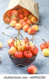 Red and yellow Rainier cherries with drops of water in a clay bowl on the gray concrete surface. Selective focus