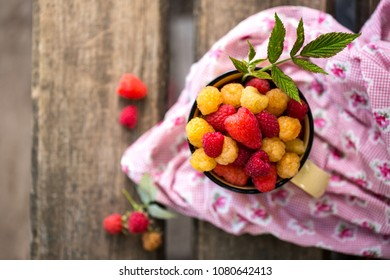 red and yellow raspberries in a cup