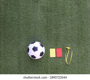 red and yellow referee soccer card isolated on green grass