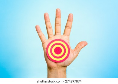 Red and yellow shooting range target on palm of hand, with blue background. Achieving goal concept.