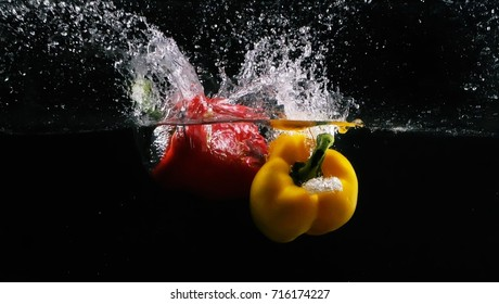 red and yellow sweet pepper fall on water