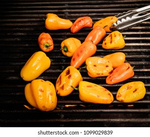 Red and yellow sweet peppers being charred on a grill with a pair of pinchers flipping them.